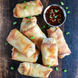 overhead shot of Crispy Baked Egg Rolls on serving board, with side of dipping sauce in top right hand corner