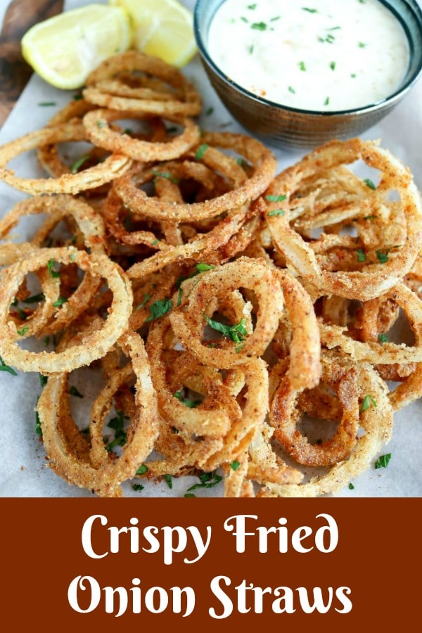 overhead shot of Crispy Fried Onion Straws with lemon wedges and side of dipping sauce at the top