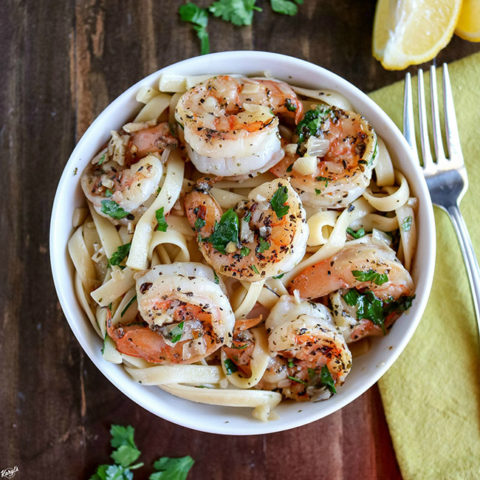 overhead shot of shrimp scampi in white bowl with napkin and fork on the side