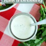 overhead shot of a glass jar of coconut milk ranch dressing with a spoon in the jar