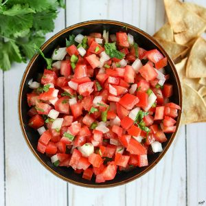 overhead shot of Pico de Gallo with chips on the right side and cilantro on left side