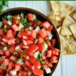 overhead shot of finished pico de gallo in a black bowl with chips on the side