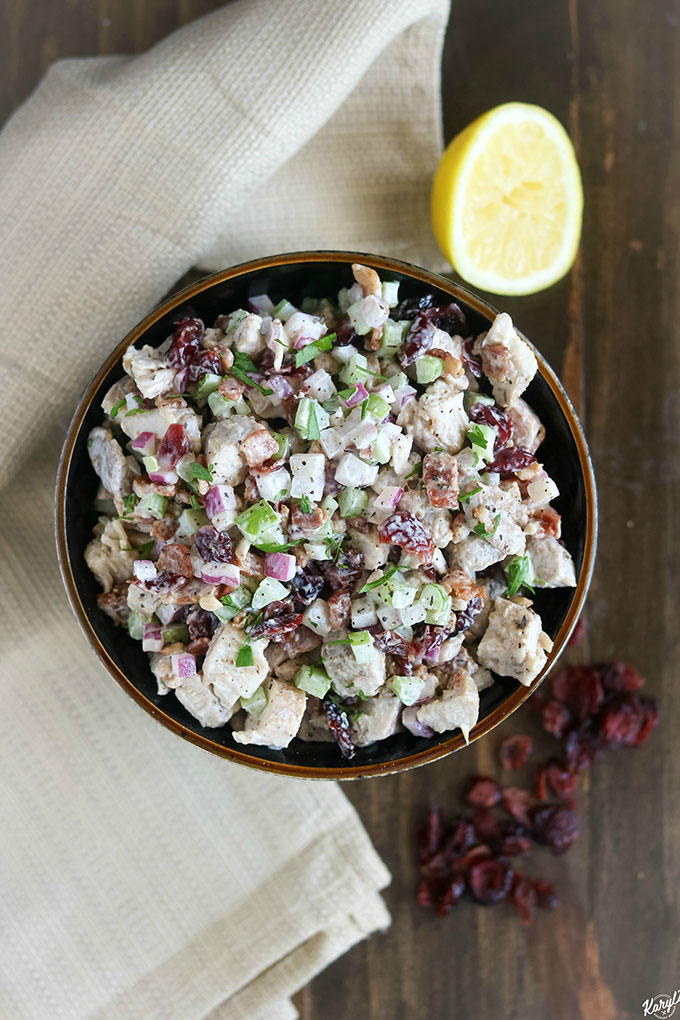 overhead shot of chicken salad in a black bowl with a tan napkin on the side, plus cranberries and a lemon wedge garnish