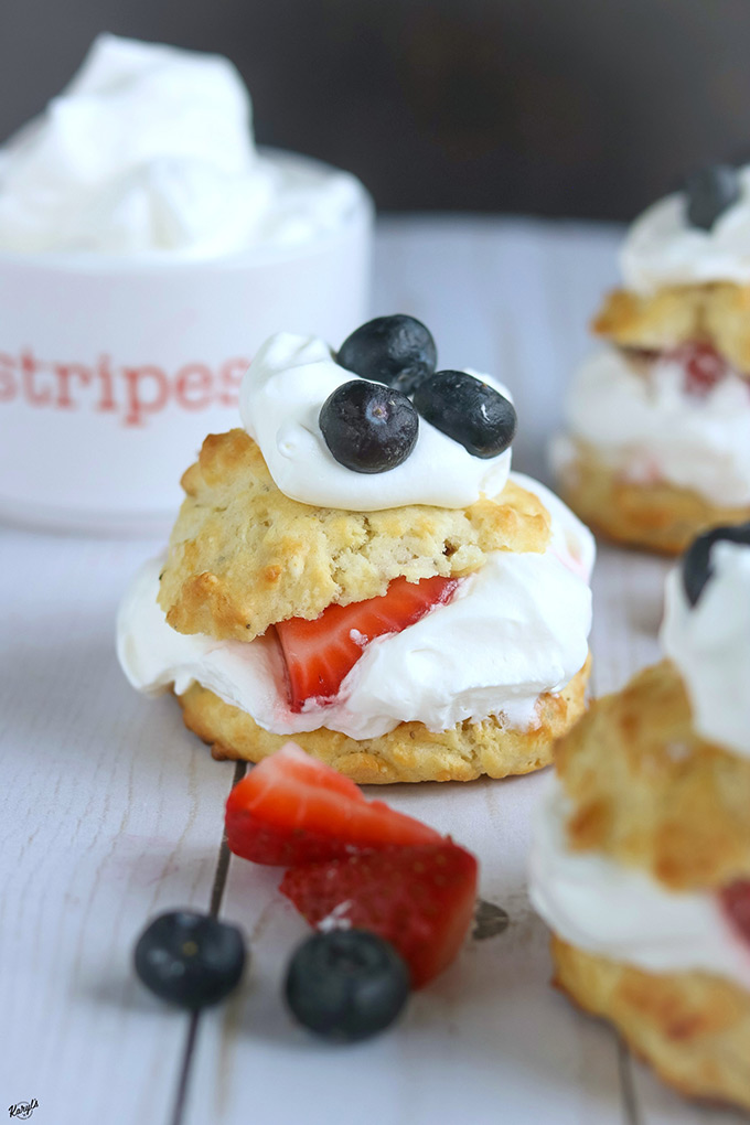 head on shot of finished shortcake, with strawberries and blueberries in foreground
