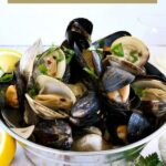 Angled shot of finished clams & mussels in a metal bucket