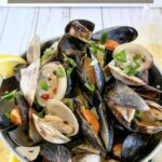 close up angled shot of finished clams & mussels in a metal bucket