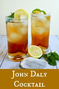2 glasses of John Daly Cocktail with lemon, tea bags and mint in the front