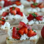 close up shot of finished bruschetta on a wooden board