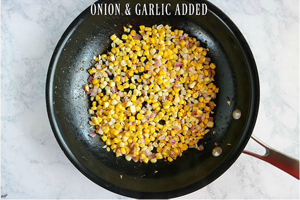 overhead shot of corn, onion and garlic sauteed in a skillet