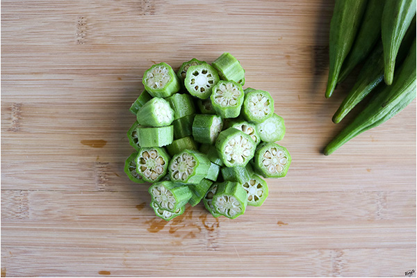 overhead process shot of cut okra on a wooden board