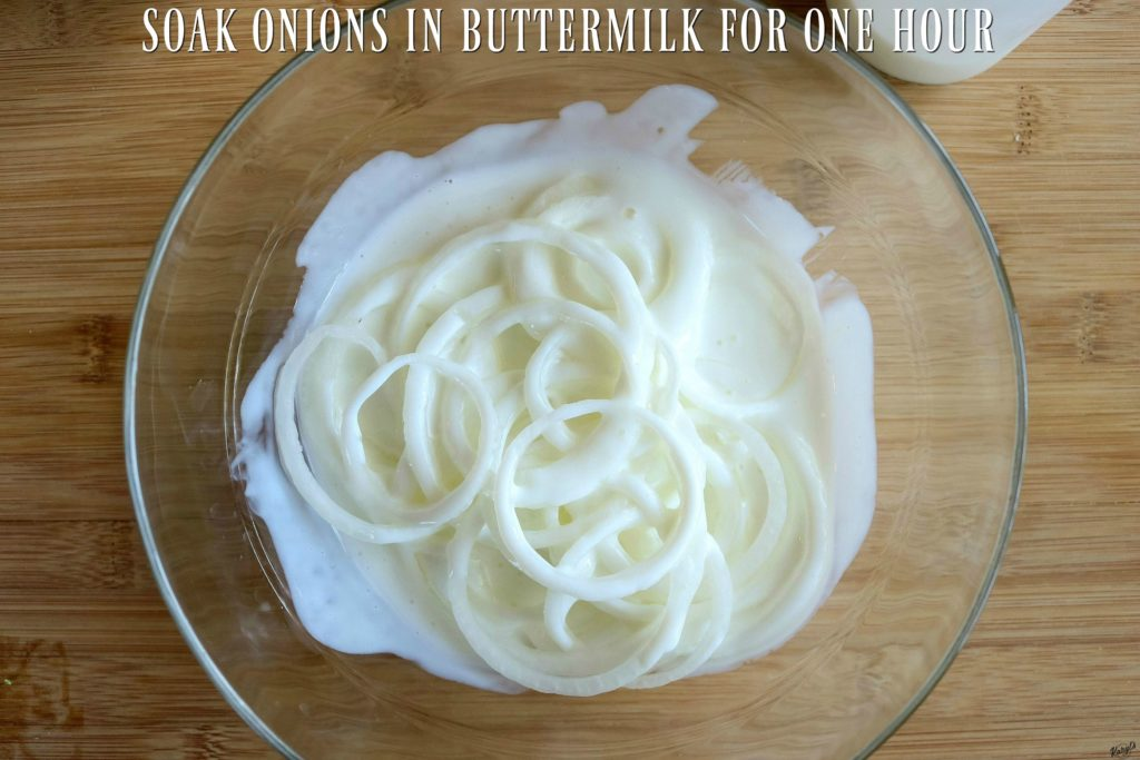 overhead shot of onions soaking in buttermilk in a glass bowl
