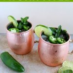 shot of 2 finished mules in copper cups with jalapeno, mint and lime on the side