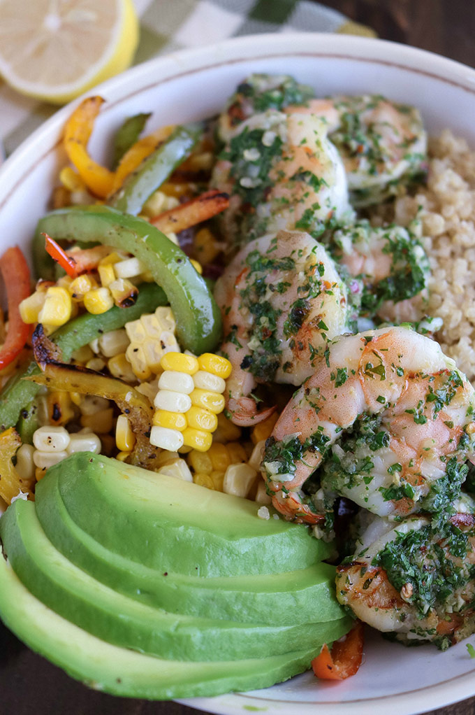 close up shot of Chimichurri Shrimp Vegetable Bowl in a white bowl with a lemon wedge in the background