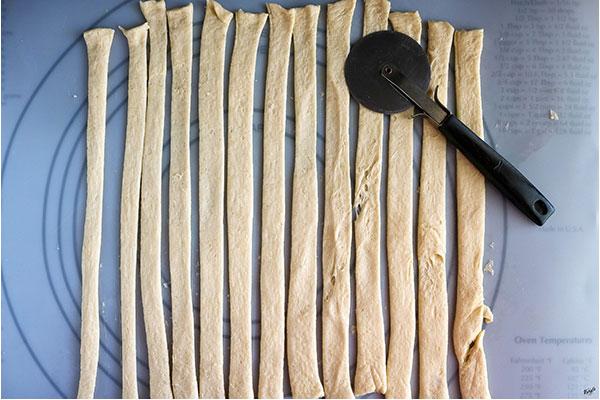 process shot: overhead shot of crescent dough sheet cut into strips