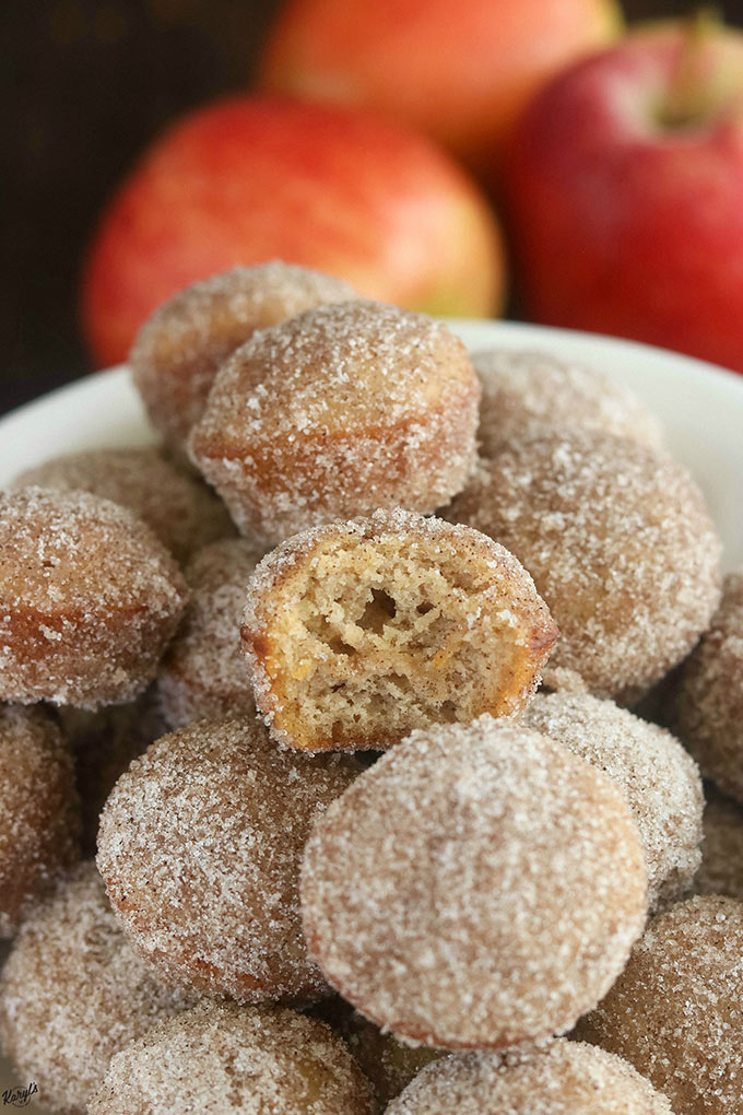 close up shot of apple cider donut holes on a white platter, with one donut hole in half
