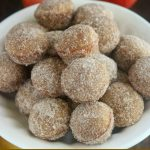 close up angled shot of donut holes in a white bowl
