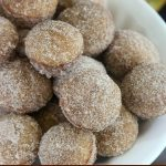 close up off-center shot of a bowl of finished donut holes win a white bowl
