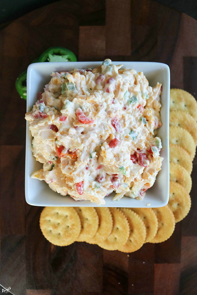 overhead shot of finished pimiento cheese in a white bowl with crackers on the side
