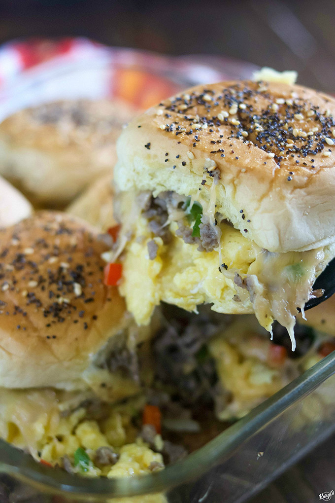 close up shot of finished loaded breakfast sliders in baking dish, with one out of the pan