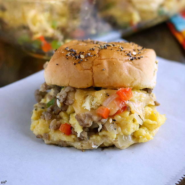 close up shot of loaded breakfast slider in front of baking dish of sliders