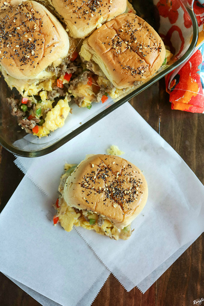 overhead shot of loaded breakfast sliders in a baking dish, with one slider out of the dish on white paper