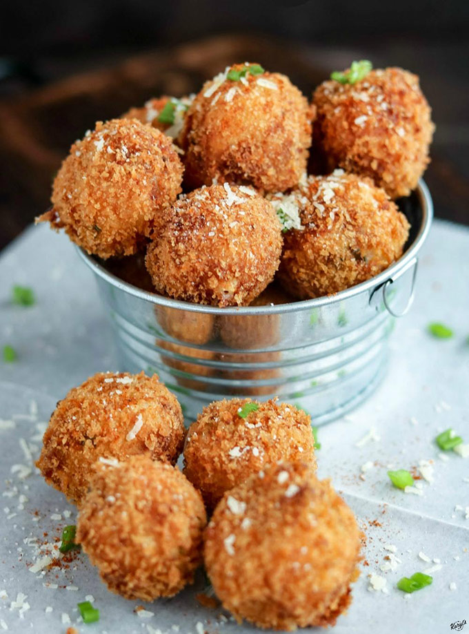 close up shot of finished mashed potato balls in a metal bucket, with a few balls on the parchment paper