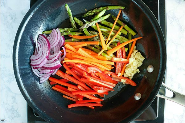 overhead process shot of vegetables added to skillet