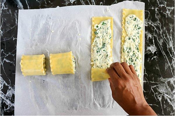 overhead process shot: rolling lasagna noodles into rolls