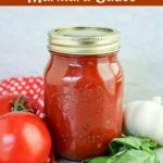 front show of marinara sauce in a sealed mason jar with fresh tomatoes, garlic and basil on the side