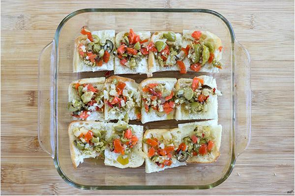 overhead process shot: olive salad on top of slider buns