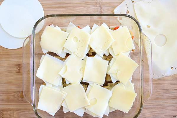 overhead process shot: provolone and Swiss cheese layered on top of olive spread