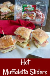 overhead shot of Hot Muffaletta Sliders on white paper with a bag of Genoa salami in the background