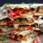 close up shot of a stack of Steak Fajita Quesadillas on a board
