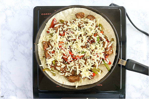 overhead process shot: steak/onion/pepper filling topped with cheese in a black skillet