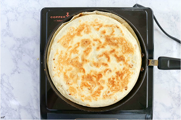 overhead process shot: quesadilla flipped over inside of black skillet