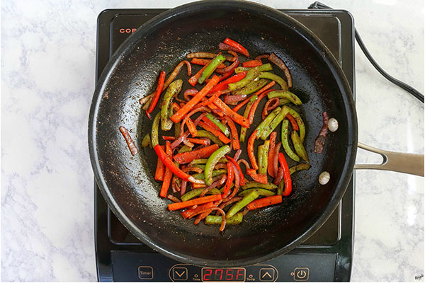 overhead process shot: onion and bell peppers in a black skillet, seasoned and sauteed until softened
