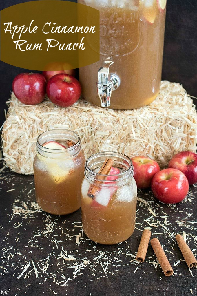 finished rum punch in Mason jars plus dispenser full of rum punch in background on top of a hay bale. Apples and cinnamon sticks as props in the background