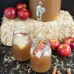 2 mason jars of rum punch with apples and cinnamon sticks in the background, plus a mini hay bale and container of rum punch on top