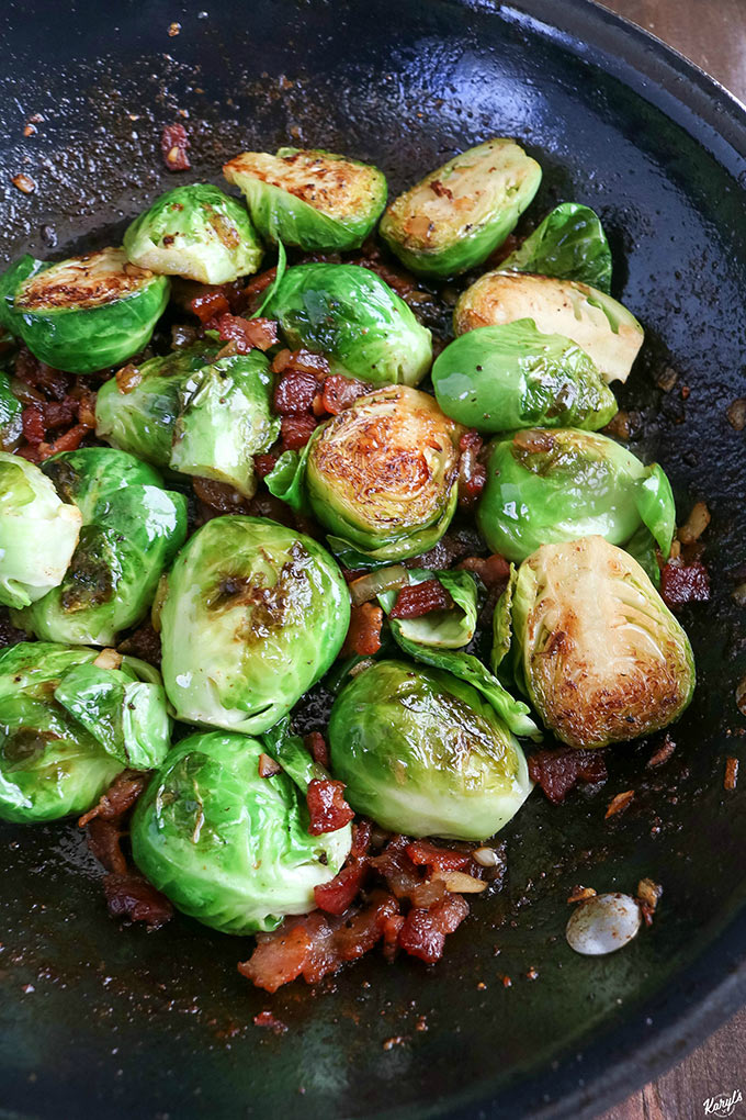 close up shot of finished Bourbon Bacon Brussel Sprouts in a black skillet