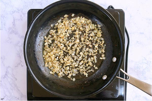 overhead process shot: minced onion and garlic sauteed in a skillet