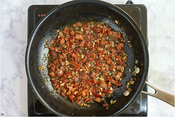 overhead process shot: bacon and spices added to garlic and onion in a black skillet