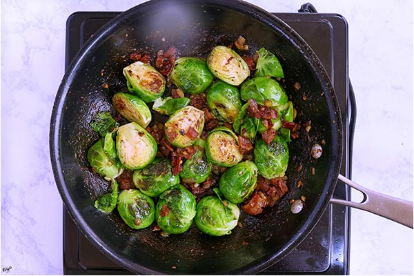 overhead process shots: bourbon bacon sauce added back to skillet with brussel sprouts