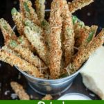 close up angle shot of finished Baked Green Bean Fries in a metal bucket with a chunk of Parmesan on the side