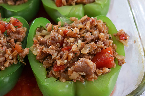 Process shot: bell peppers stuffed with mixture in a glass baking dish