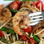 close up shot of spicy garlic shrimp pasta with a piece of shrimp on a fork