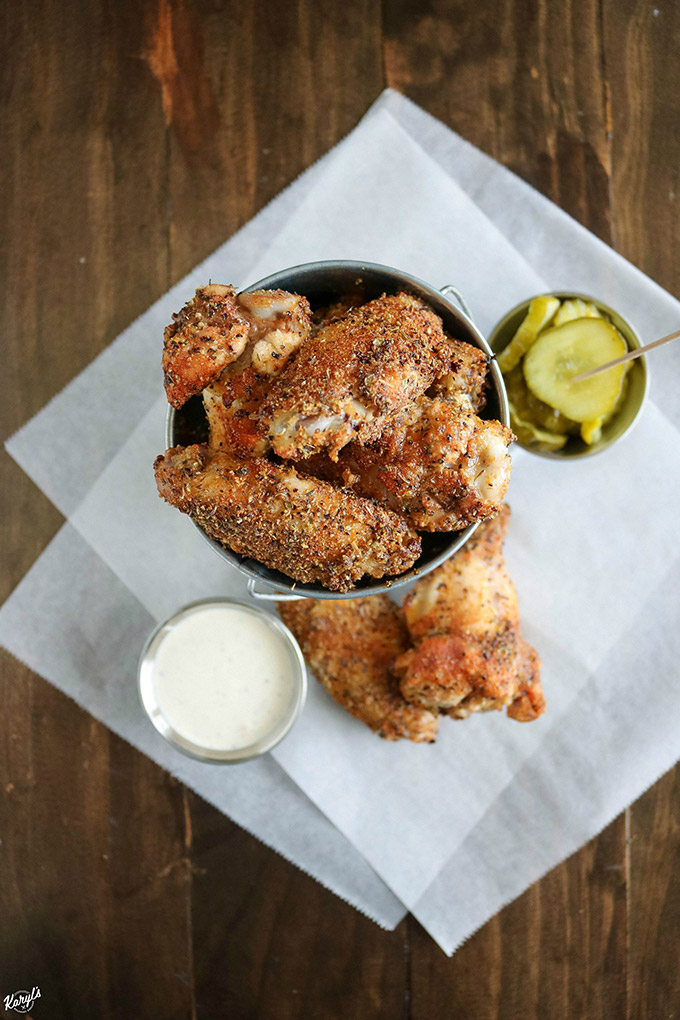 overhead shot of finished chicken wings in a metal bucket, with dip and pickles on the side