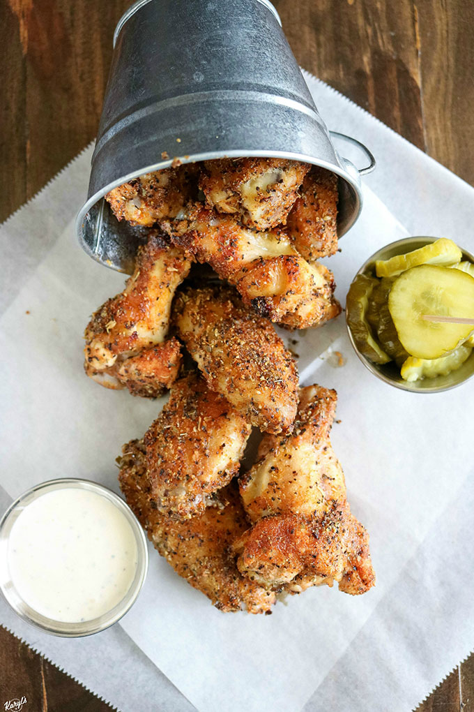 overhead shot of finished chicken wings falling out of a metal bucket onto white paper, with dip and pickles on the side