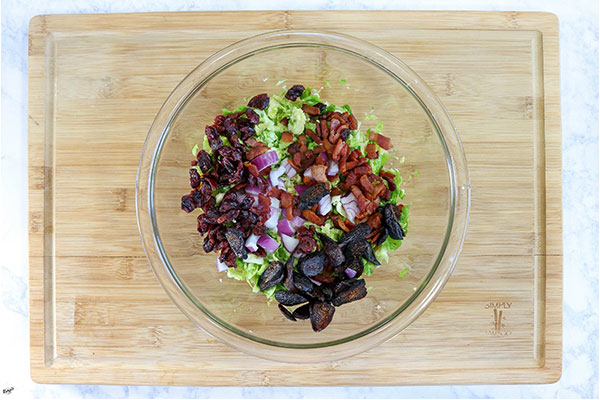 overhead process shot: brussel sprouts, onion, figs, bacon and cranberries in a bowl