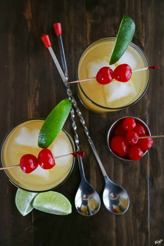 overhead shot of 2 Black Eyed Susans with 2 spoon in the middle with cherries and lime wedges on the side