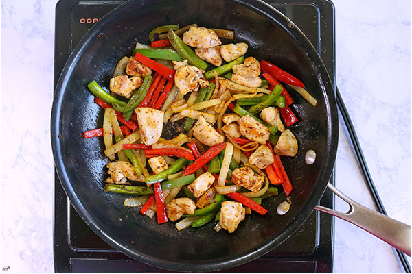 overhead process shot of veggies and chicken, mixed with fajita seasoning, in a black skillet